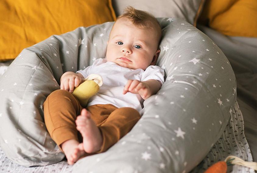 miminko leží uložené v kojicím polštáři